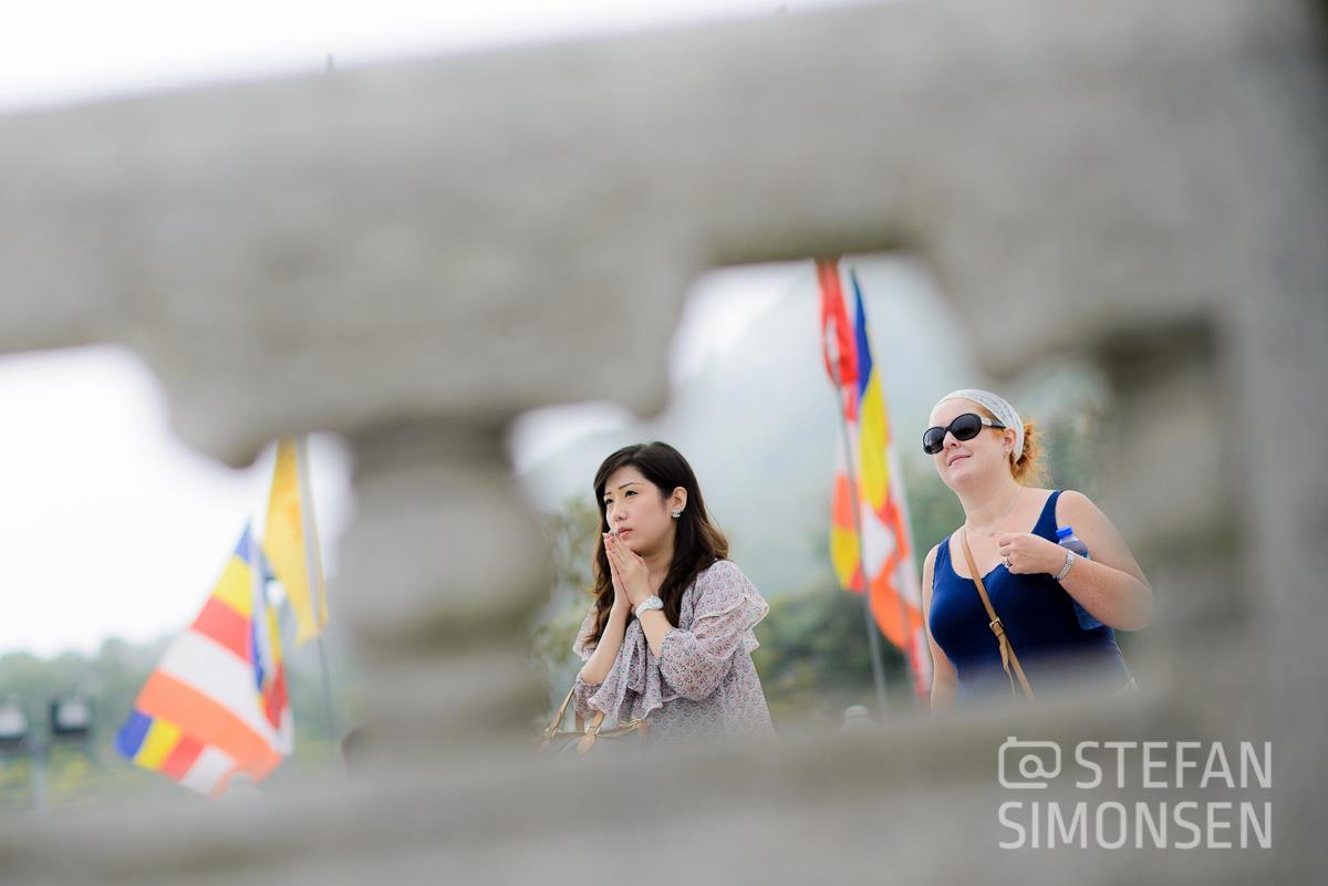 Eine Touristin beobachtet eine betende Frau am Tian Tan Buddha, Lantau Island, Hongkong