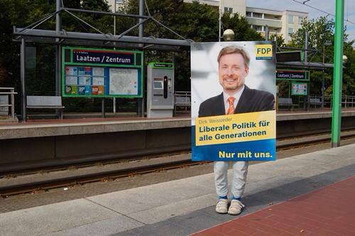 Ein Mädchen hält ein Plakat des FDP-Lokalpolitikers Dirk Weissleder fest