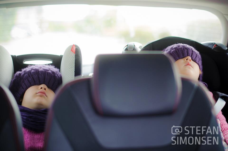 Zwei Kinder schlafen im Auto in ihren Kindersitzen nach einem Familien-Fotoshooting